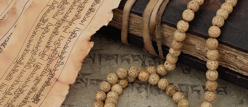 A traditional Tibetan Buddhist book, and a mala – beads used to count mantras during meditation