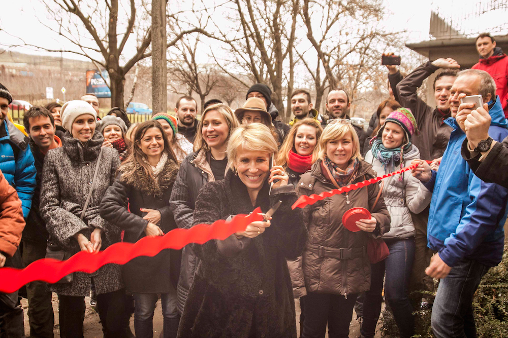 Caty Hartung with Lama Ole on the phone symbolically cuts the ribbon of a future new Buddhist Center in Bratislava.